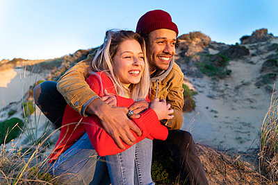 Man wearing knit hat embracing beautiful woman while sitting on sand dune - p300m2267252 by Steve Brookland