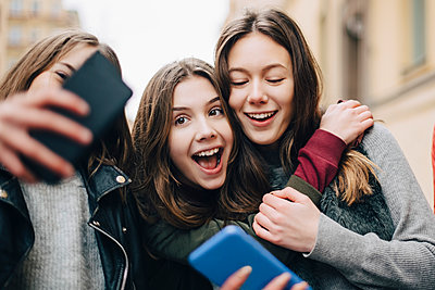 Girl taking selfie with female friends through mobile phone in city - p426m1555957 by Maskot