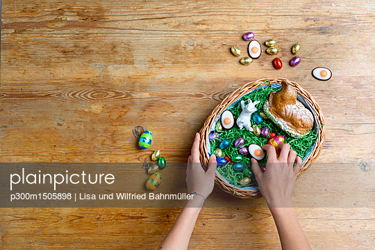 plainpicture | Photo library for authentic images - plainpicture p300m1505898 - Hands filling Easter nest - plainpicture/Westend61/Lisa und Wilfried Bahnmüller