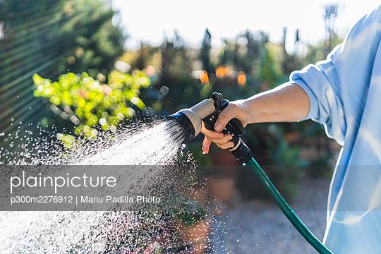 Woman watering with garden hose at front yard - p300m2276912 by Manu Padilla Photo
