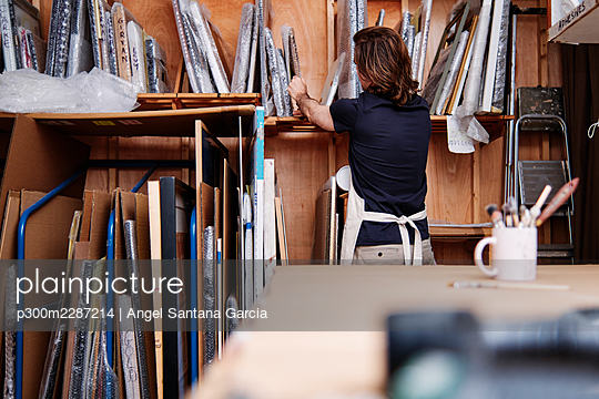 Male store owner removing picture frame from shelf while working at workshop - p300m2287214 by Angel Santana Garcia