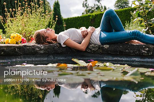 Young woman lies asleep alongside fountain - p586m1110106 by Kniel Synnatzschke