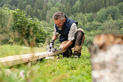 Carpenter sawing plank with circular saw - p300m2243432 by Vasily Pindyurin