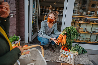 Store owner presenting carrots to customer at organic food store, Cologne, NRW, Germany - p300m2256154 von Mareen Fischinger