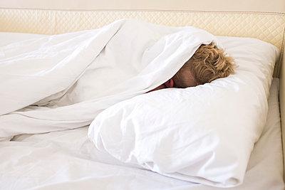 Junge versteckt sich unter der Bettdecke - p890m1467389 von Mielek