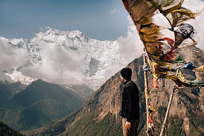 Hiker on peak, Annapurna Circuit,  view to Annapurna 2 mountain, the Himalayas, Manang, Nepal - p924m2018567 by Sara Monika
