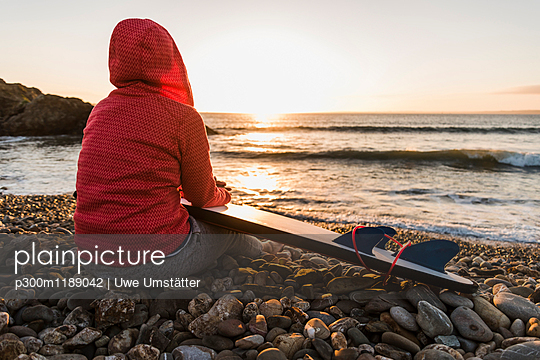 France, Bretagne, Crozon peninsula, woman sitting on stony beach at sunset with surfboard - p300m1189042 by Uwe Umstätter