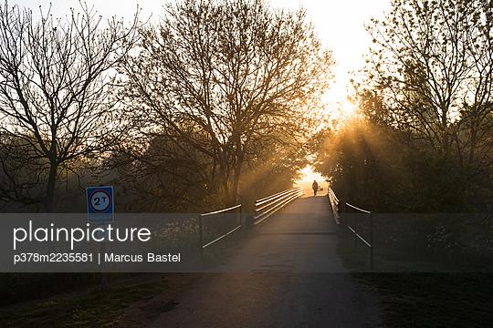 Figure crossing bridge at sunrise - p378m2235581 by Marcus Bastel