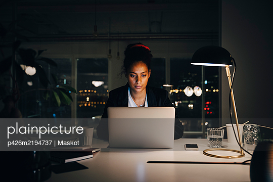 Dedicated young businesswoman working late while using laptop at creative office - p426m2194737 by Maskot