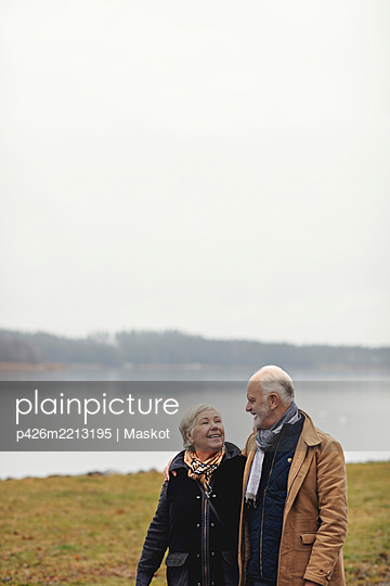 Smiling senior couple looking at each other while standing by lake against clear sky - p426m2213195 by Maskot
