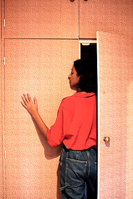 Young woman in red blouse coming out of a closet - p1521m2128953 by Charlotte Zobel