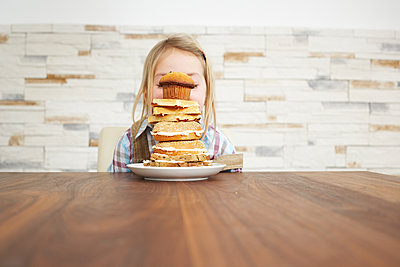 Little girl behind stack of baked goods - p300m1460425 by Sandra Seckinger