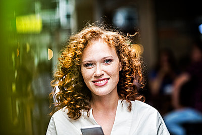 Portrait of smiling young woman with cell phone - p300m1505752 by Jo Kirchherr