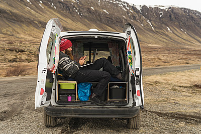Iceland, man sitting in van using smartphone and laptop - p300m1587585 by VITTA GALLERY