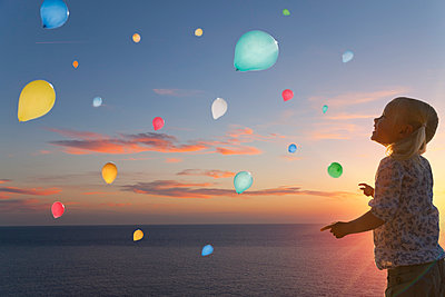 Girl watching balloons floating in evening sky - p429m1014402 by Henglein and Steets