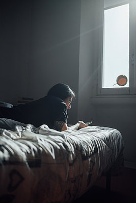 Woman with tattooed arm lying on bed, using mobile phone during Corona virus crisis. - p429m2183361 by Eugenio Marongiu
