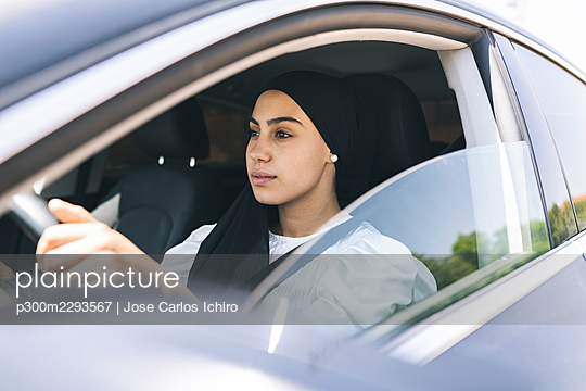 Young woman driving car - p300m2293567 by Jose Carlos Ichiro