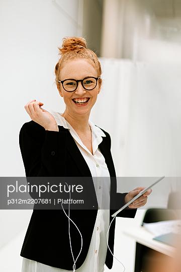 Woman holding digital tablet in office - p312m2207681 by Plattform