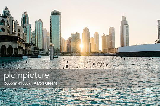 Sunset over city skyline, Dubai, United Arab Emirates - p555m1410087 by Aaron Greene