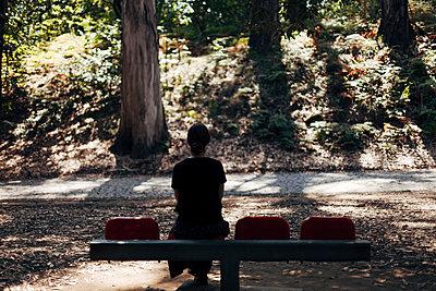 Frau sitzt allein auf einer Bank im Park - p1340m2108701 von Christoph Lodewick