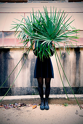 Woman in black dress holding palm leaves - p1521m2228359 by Charlotte Zobel