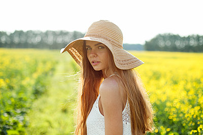 Young woman in a rape field - p1646m2227381 by Slava Chistyakov