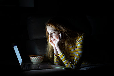 Young woman lying on the couch at home using laptop - p300m2170113 by VITTA GALLERY