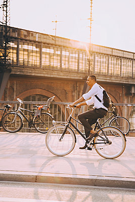 Full length of businessman riding bicycle on street in city against sky - p426m2169402 by Maskot