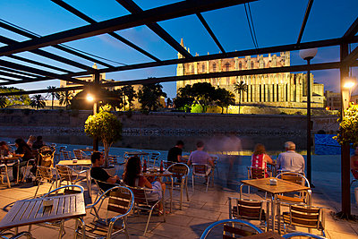 People in cafe beside Parc del Mar with cathedral behind; Palma, Majorca, Spain - p442m840101 by Ian Cumming