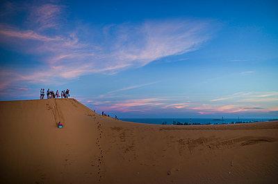 Friends slide down a dune over an improvised sled, Mui Ne, Binh Thuan Province, Vietnam, Southeast Asia - p934m1177104 by Sebastien Loffler