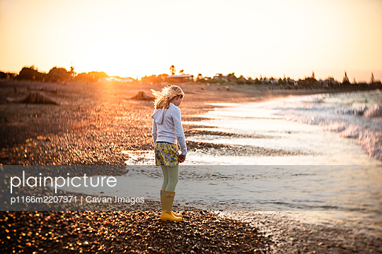 Tween girl on rocky New Zealand beach at sunset - p1166m2207971 by Cavan Images