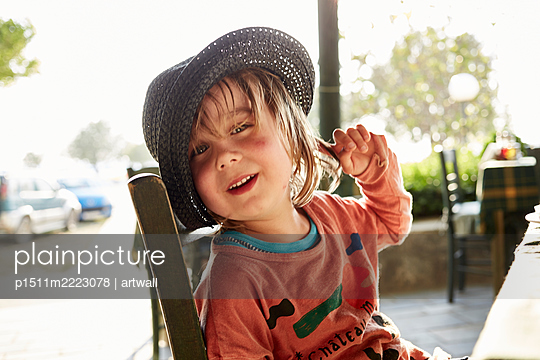 Blond boy with straw hat in a restaurant - p1511m2223078 by artwall