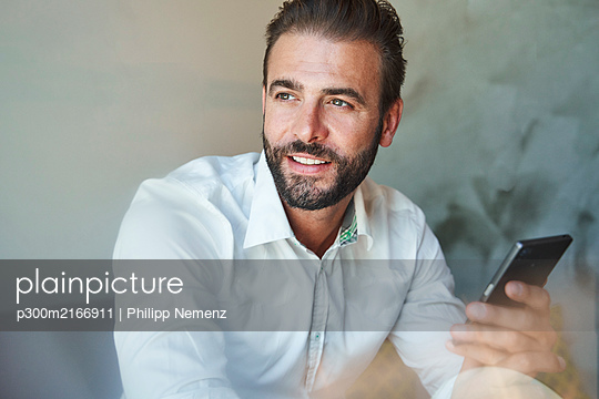 Portrait of smiling businessman wearing white shirt holding cell phone - p300m2166911 by Philipp Nemenz