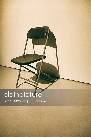 Folding chair against wall - p597m1425609 by Tim Robinson