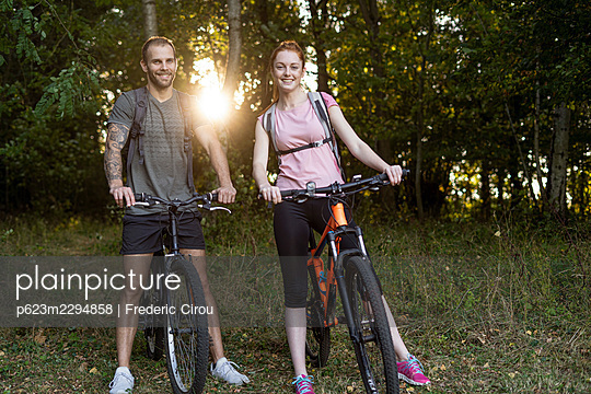 Smiling young couple standing with bicycles in forest - p623m2294858 by Frederic Cirou