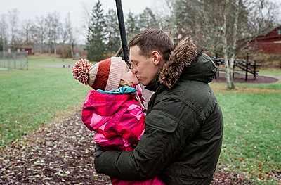 father kissing his daughter whilst playing outside in a park - p1166m2148887 by Cavan Images