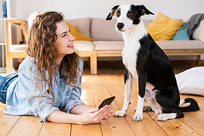 Beautiful woman with long hair holding smart phone while looking at dog in living room - p300m2276500 by Steve Brookland