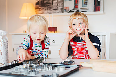 Two boys playing with cookie cutters at home - p312m1164550 by Rebecca Wallin