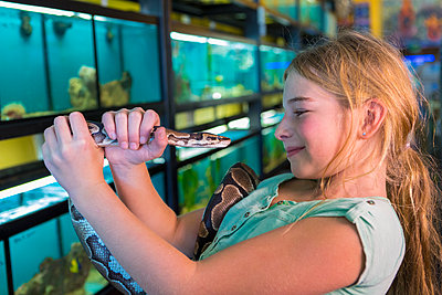Caucasian girl admiring snake in pet store - p555m1410485 by Marc Romanelli