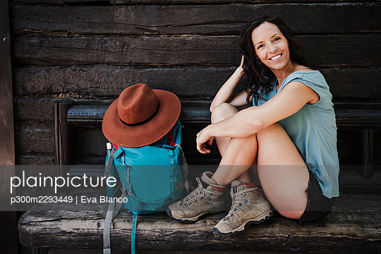 Happy woman with hand in hair sitting by backpack on bench outside cottage - p300m2293449 by Eva Blanco