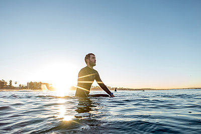 Thoughtful surfer sitting on surfboard in sea against clear sky during sunset - p1166m1414546 by Cavan Images