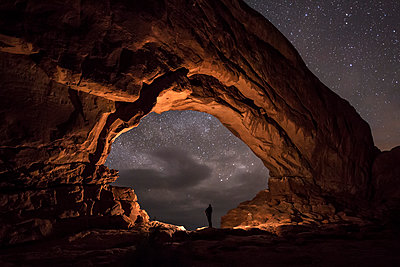Person stands in an archway and the night sky - p1424m1500859 by Brad Goldpaint
