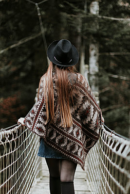 Back view of fashionable young woman wearing hat and poncho walking on suspension bridge - p300m1549839 by Oriol Castelló Arroyo