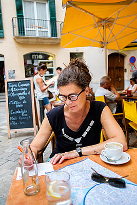Spain, Mallorca, Las Palmas, Mature woman writing at table in restaurant - p352m1186963 by Lena Katarina Johansson