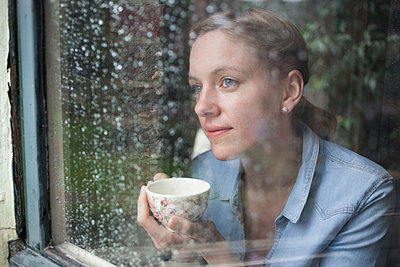 Young woman looking out of a window - p586m933110 by Kniel Synnatzschke