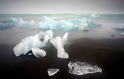 Icebergs from the Jokulsarlon glacial lagoon washed up on a nearby black volcanic sand beach from the North Atlantic Ocean, Iceland, Polar Regions - p871m1073117f by Lee Frost