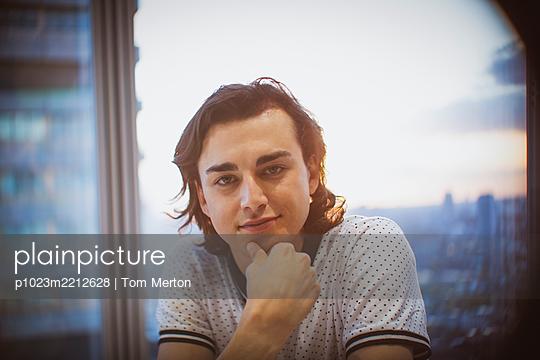 Portrait confident businessman in highrise office - p1023m2212628 by Tom Merton