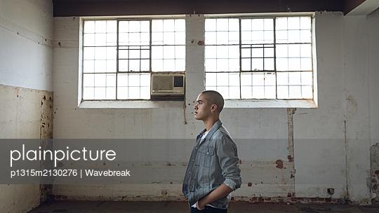 Young man inside an empty warehouse - p1315m2130276 by Wavebreak