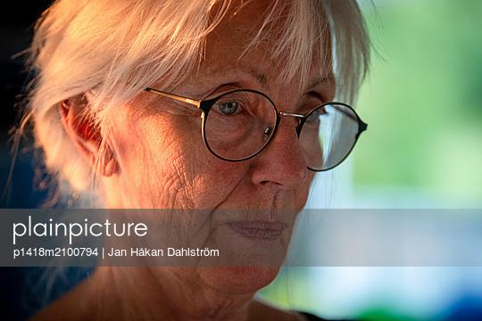 Ältere Frau in Sonnenstrahlen - p1418m2100794 von Jan Håkan Dahlström