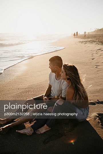 Happy young couple sitting on the beach at sunset - p300m2132268 by letizia haessig photography